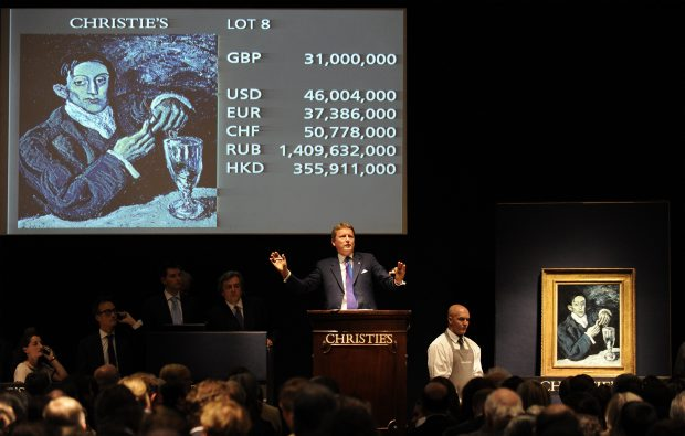 Christies' auctioneer Jussi Pylkkanen gestures near Pablo Picasso's 1903 painting 'Portrait of Angel Fernandez de Soto' during an auction of Impressionist and Modern Art in London on Wednesday. Photograph by: Paul Hackett, Reuters z