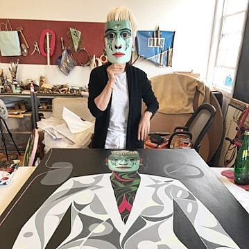 Wearing the TlayilelaMetamorphosis Mask standing in front of painting Bothhellip