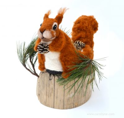 "Squirrel: Nature's Natural Gardener, Needle felting wool, reindeer slipper, beach combed timber, locally foraged pine fronds and cones, 13"" x 17"" x 15"", 2018."