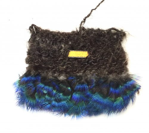 Protective Gear 2, 9″ x7″ x 1.25″, 2020, knitted human hair, reflector, peafowl feathers. 6″ x 6″ 2″