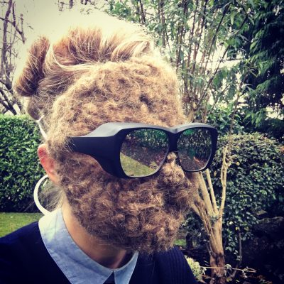 Carollyne wearing her needle felted hair mask and dichromatic spectacles in the garden